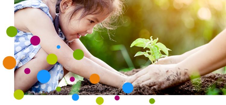 Mädchen pflanzt mit Hilfe eines Erwachsenen
